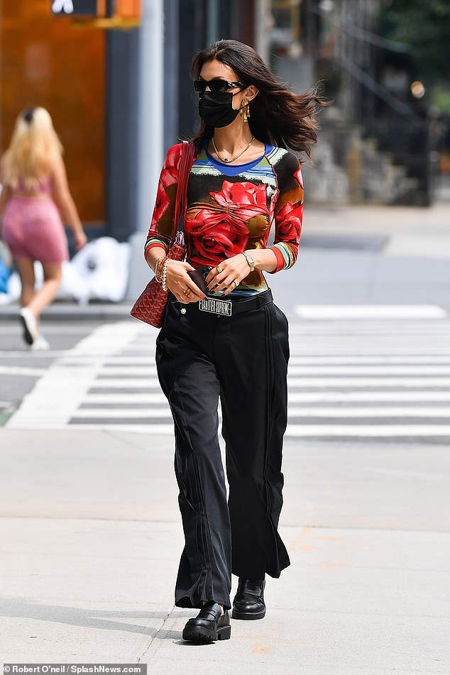 Back in black: Bella contrasted her colorful top with black pleated pants and a Supreme X Jean Paul Gaultier belt