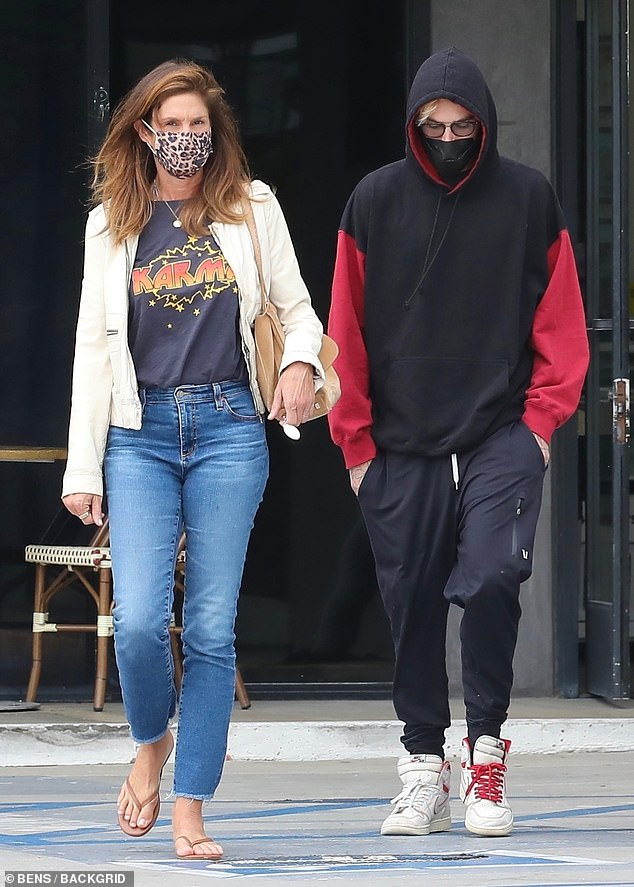 Stocking up: Cindy Crawford, 55, looked casual and youthful in a graphic T-shirt and a white jacket while doing some shopping at the Malibu Mall Plaza with her son Presley Gerber, 22