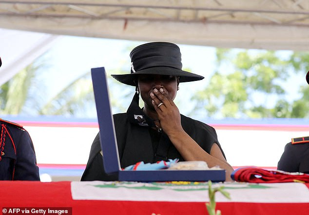 Martine Moise, the wife of slain president Jovenel, weeps over his casket during his funeral - before saying his killer 'are still running the streets'