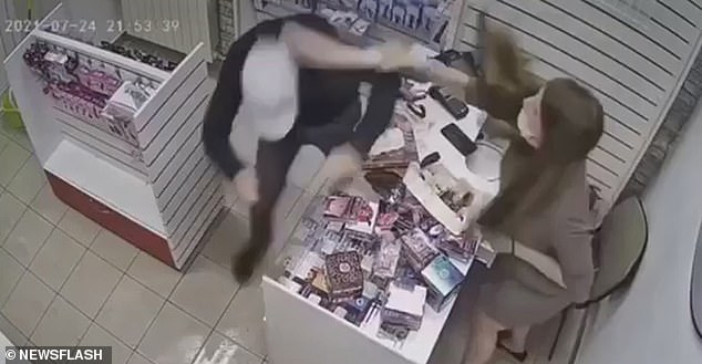 The saleswoman pretends to bend down to get something with her right hand while slyly sliding her left towards a rubber dildo on the counter, which she uses to whack the thief over the head