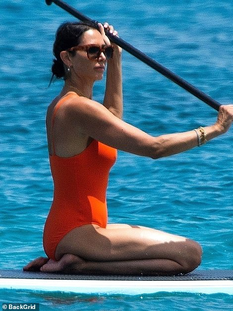 Holiday mode: She swept her raven tresses back in a sleek bun and shielded her eyes from the Caribbean sun with angular sunglasses