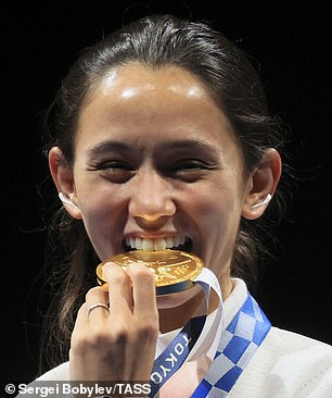 Team USA's gold medallist Lee Kiefer, 27, bit into her medal at a victory ceremony for the women's foil fencing individual event