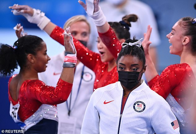 Waiting game: Biles, who is the oldest member of the team and the only returning Olympian on the squad, stood by to support her fellow athletes as they continued the competition