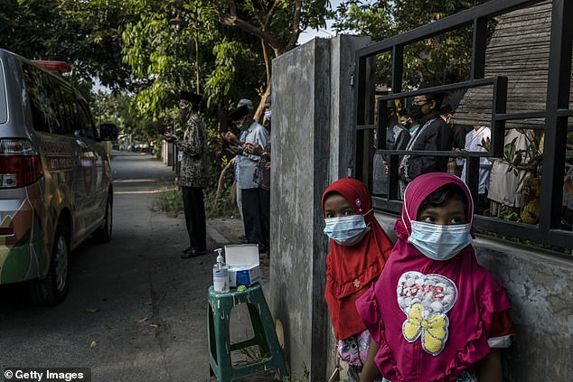 Two Indonesian girls are seen as families pray next to an ambulance in Covid-strickenYogyakarta, Indonesia (pictured on July 22). The nation has imposed emergency restrictions on 15 locations beyond Java and Bali, aiming to tame the recent Covid-19 surge
