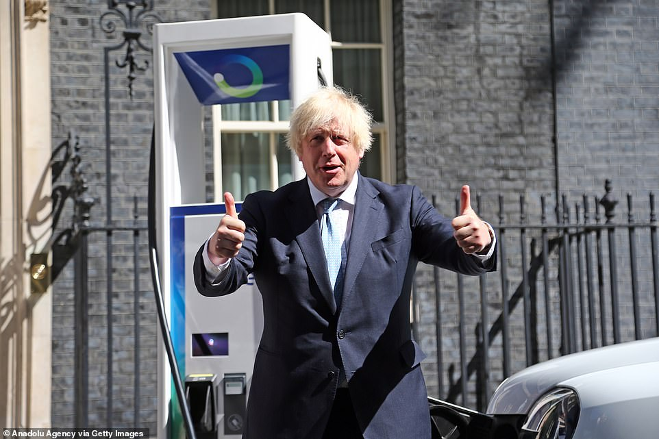 One of the Government's top scientific advisers yesterday said he advised ministers to adopt a 'test and release' strategy as early as January, but Boris Johnson (pictured posing next to some electric cars outside 10 Downing Street this morning) has so far refused to budge on the August 16 date for scrapping self-isolation for the double-jabbed