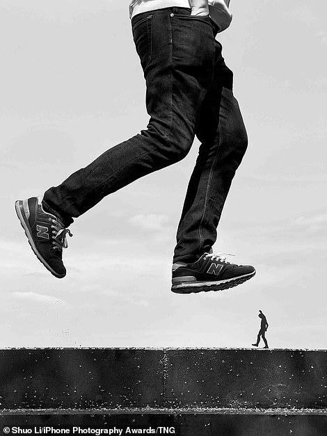 Shuo Li's photograph shows a man in jeans and trainers jumping on a wall over a small figurine in Bejing, China