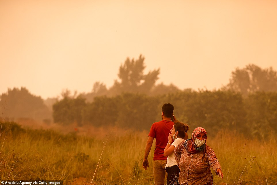 Residents flee across fields in Dolbazlar neighbourhood in Antalya, southern Turkey, on Thursday after wildfires reached them