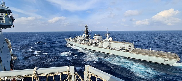 HMS Kent, a Type 23 frigate, is shown resupplying from RFA Tidespring during military exercises in the South China Sea