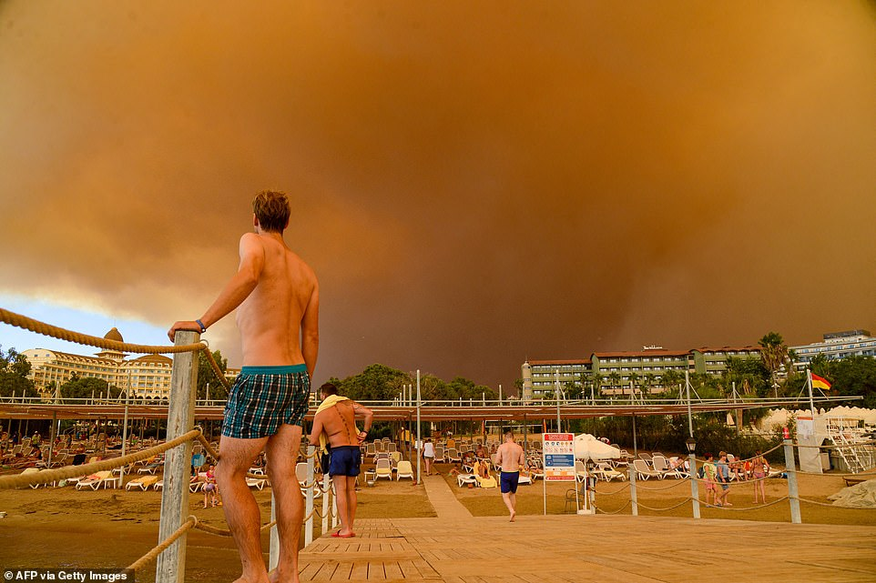Tourists were seen on the beach near the town of Manavgat in southern Turkey as dark smoke covered the sky following wildfires