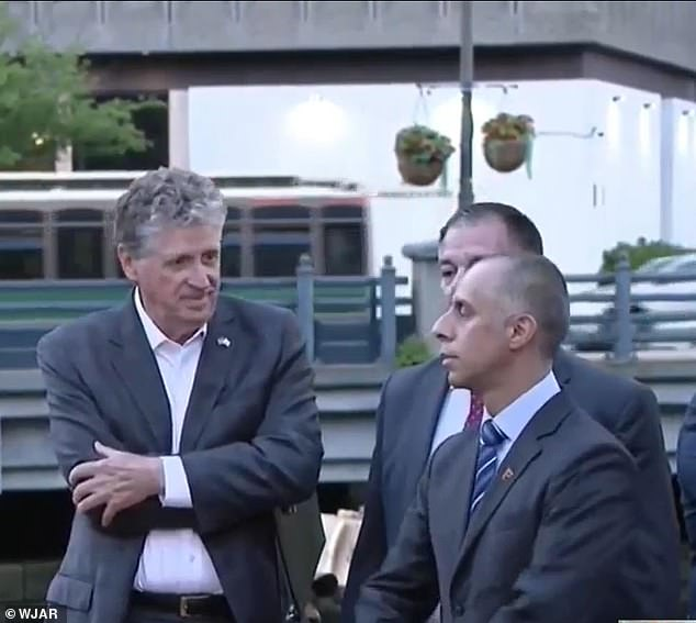 War of words: Gov Dan McKee (left) and Mayor Jorge Elorza (right) were seen talking on Wednesday before a security guard (center) was forced to intervene