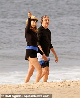 Loved up: The pair were deep in conversation as they enjoyed a stroll on the beach together to start their day