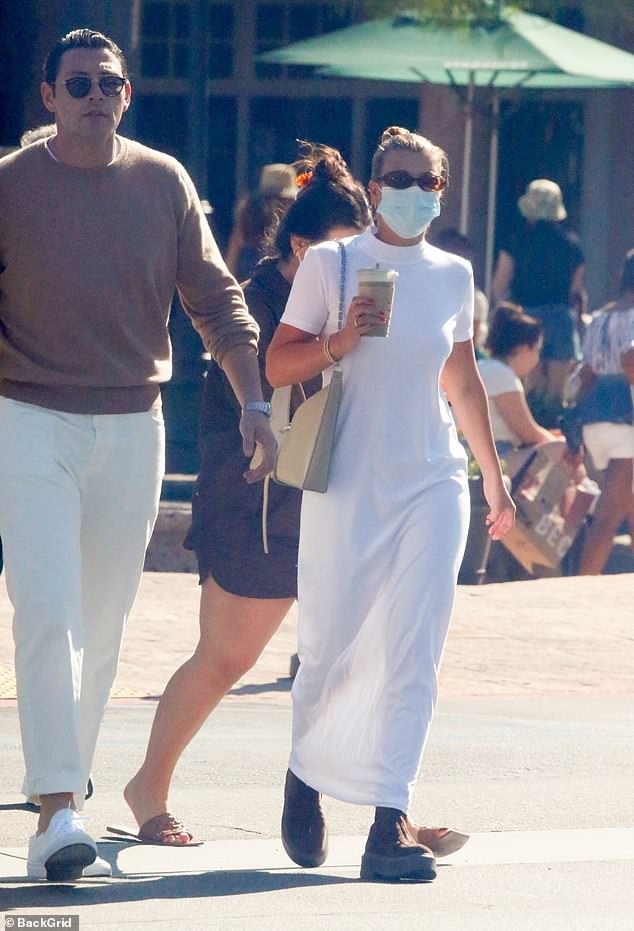 Observation: The model, 22, donned an elegant white dress, paired with beige boots for her juice run with her beau, 27