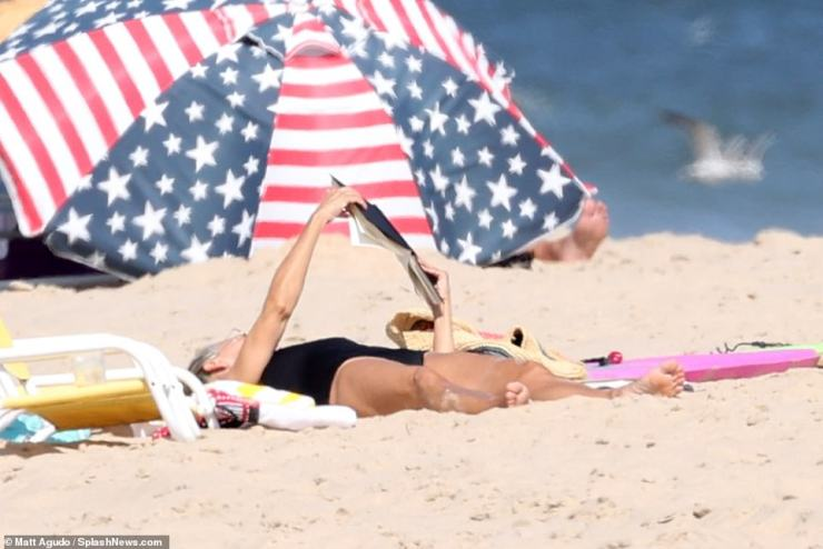 Time to read: She held up a book as she lay down on her back with a boogie board next to her