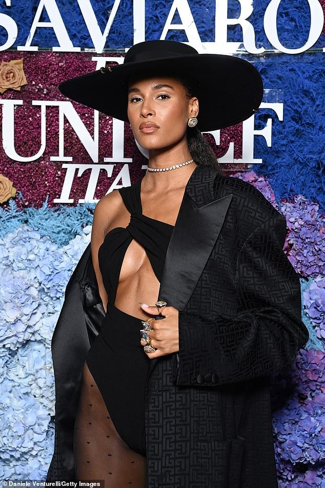 Glamorous: She swept an onyx black Balmain robe over her left shoulder