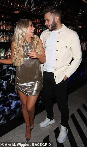 So in sync: Her outfit perfectly complemented her reality star beau Finley Tapp, who looked dapper in black jeans and an open white denim shirt