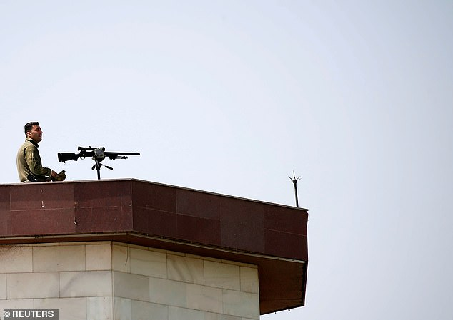 A sniper keeps a watch from the roof of the parliament building before Afghan President Ashraf Ghani arrives at parliament
