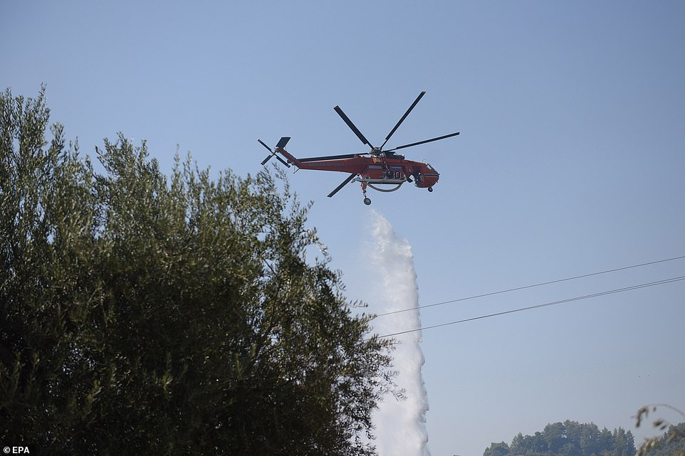 A firefighting helicopter douses a wildfire in thePeloponnese region of Greece, near the village ofZeria