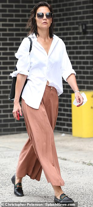 Stylish:Later in the day, Katie changed into a pair of high-waisted wide leg pleated slacks that were in a trendy rust color