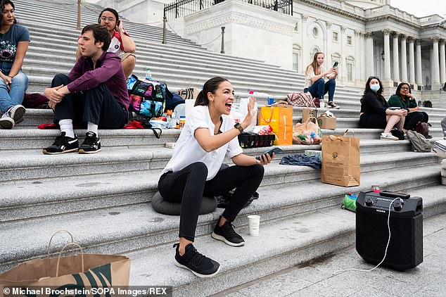 A very happy Alexandria Ocasio-Cortez (D-NY) greets others at the steps of the U.S. Capitol