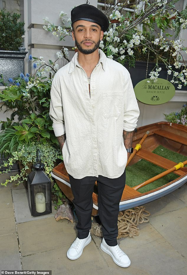 Standing solo: He wore a loose-fitting white shirt and a matching pair of trainers as he casually posed with his hands in his pockets at the bash