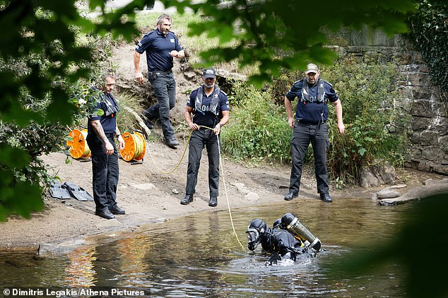 Pictured: A police diver surfaces in the bank of river Ogmore in Lower Llansantffraid in Sarn near Bridgend, Wales