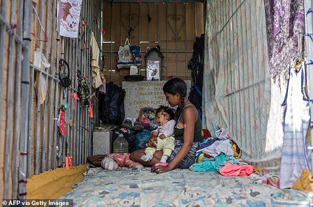A mother and her baby are forced to sleep in a cemetery in Caracas (pictured in February)