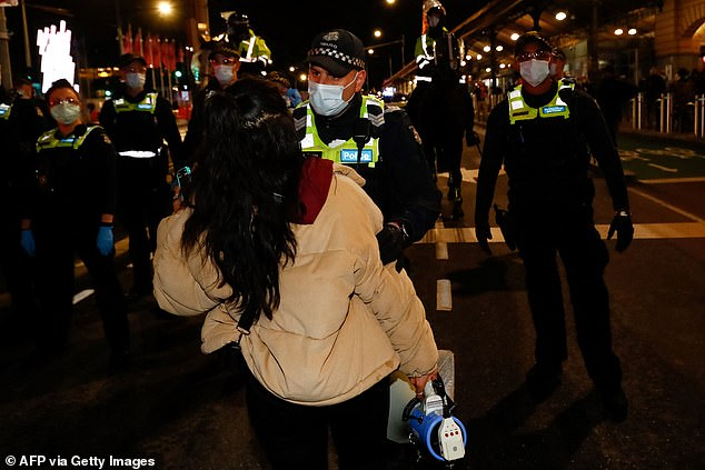 A protester with a megaphone is pictured speaking with police officers during the rally