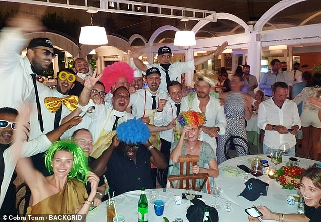 Crazy night: Dressed in her colourful wig, Katy posed for the fun group snaps during the wild evening