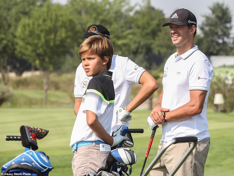 Emilio (left), who has an older and younger brother, pictured playing a round of golf with his dad Michael back in 2015