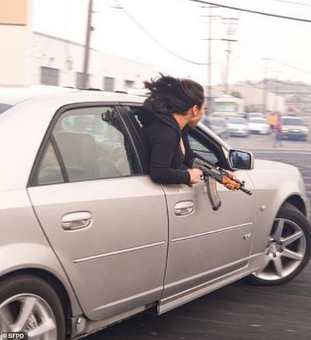 The woman - who has not been identified - leans out of a Cadillac's passenger window and brandishes an AK-47 while speeding through the streets of San Francisco