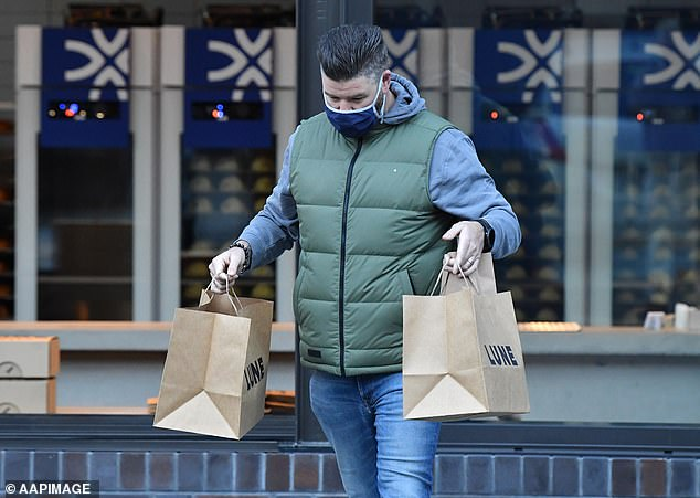 A man in Brisbane leaves with Lune Croissanterie goodies. The current lockdown in south-east Queensland is due to end this Sunday at 4pm