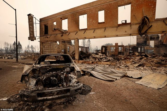 View of a burned out car and commercial building following the Dixie Fire, which swept through Greenville on Wednesday