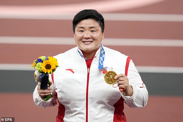 Gong proudly holding her gold medal inside the Olympic Stadium in Tokyo