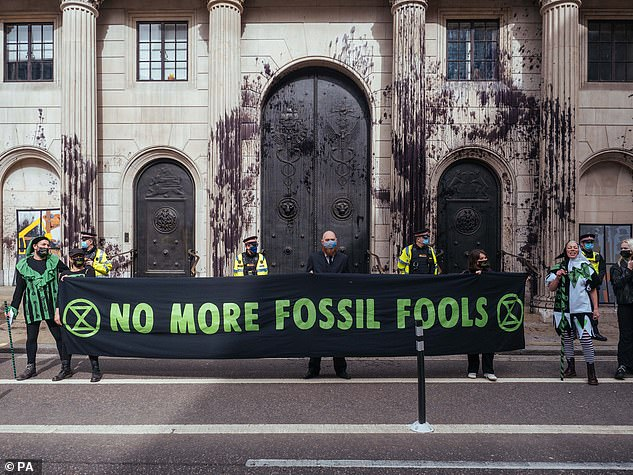 Demonstrators stand outside the Bank of England in London and protest against the role of banks in the climate crisis