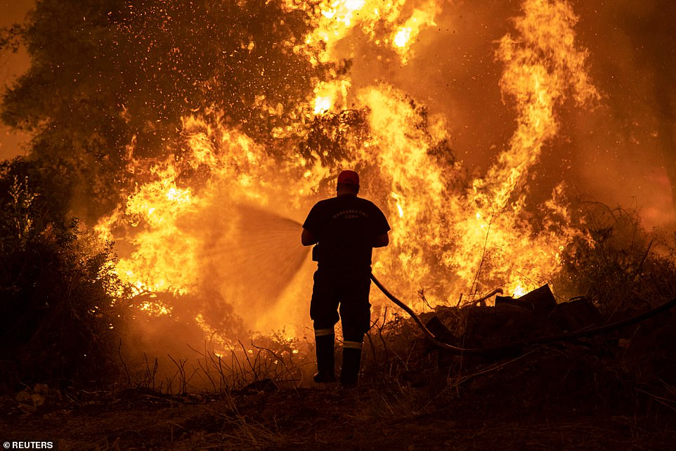 Climate change: The bombshell UN report comes as record heatwaves, wildfires and floods hit countries around the world. A firefighter is pictured above trying to extinguish a wildfire burning on the island of Evia, Greece at the weekend