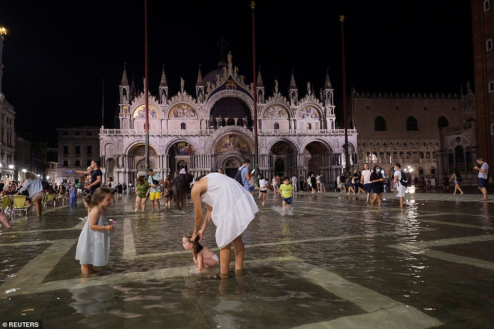 Two little girls play with their mother in flooded Piazza San Marco after flash flooding last night brought the water-level up to 3ft in some parts of Venice, Italy