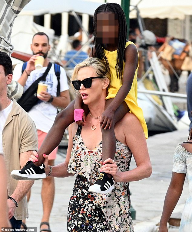 Doting mama: Charlize looked every inch the doting mother as she held onto Jackson's legs while giving her a lift around the island