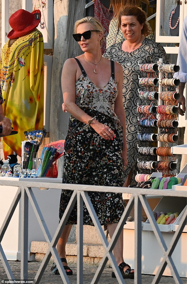 Blooming lovely!Charlize looked effortlessly stylish as she slipped into a floral wrap dress that cinched in at her slender waist and flared out to mid calf length