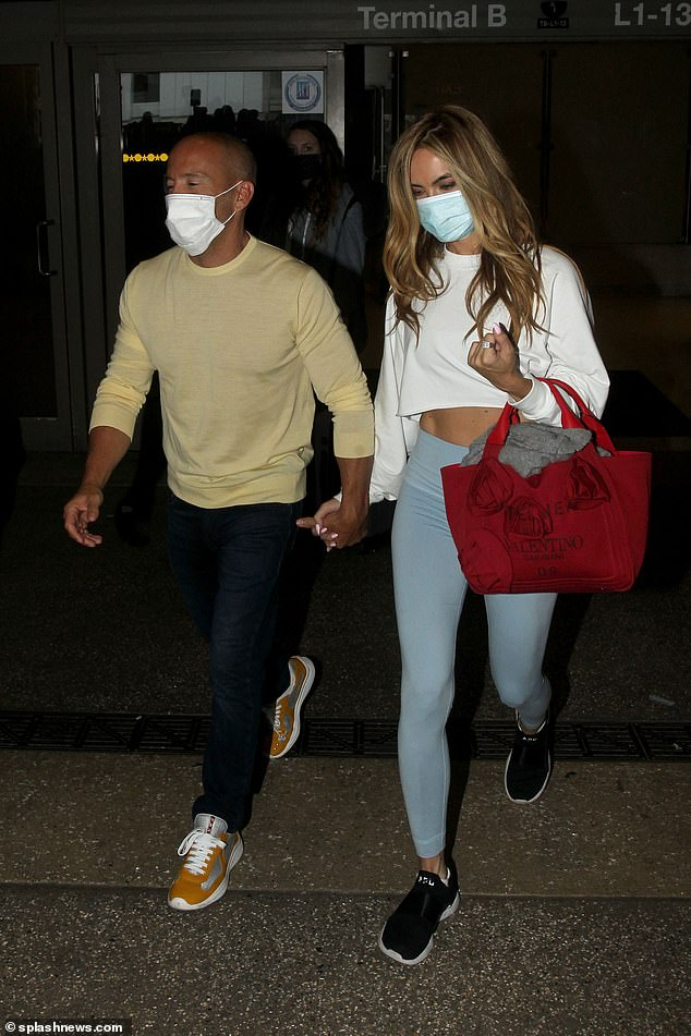 It must be love: The two were hand in hand and in step as they walked out of the airport