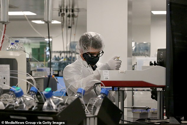 The facility will be built and operated by Moderna and will be nearly the same size as the company's factory in Norwood, Massachusetts. Pictured: A worker is seen in the preclinical manufacturing area at the Moderna facility in Norwood, May 2021