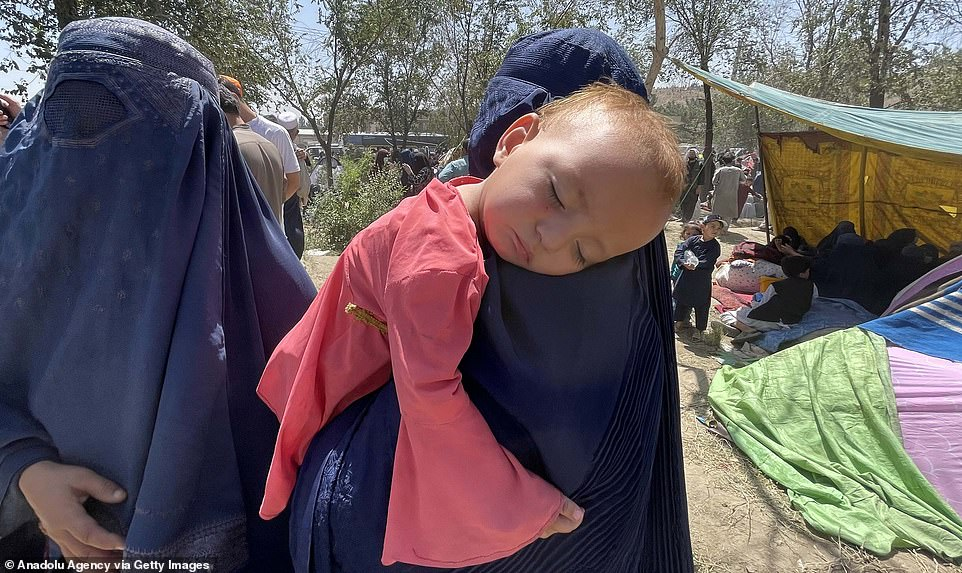 A child is pictured sleeping on its mother's shoulder at a refugee camp in the Afghan capital of Kabul