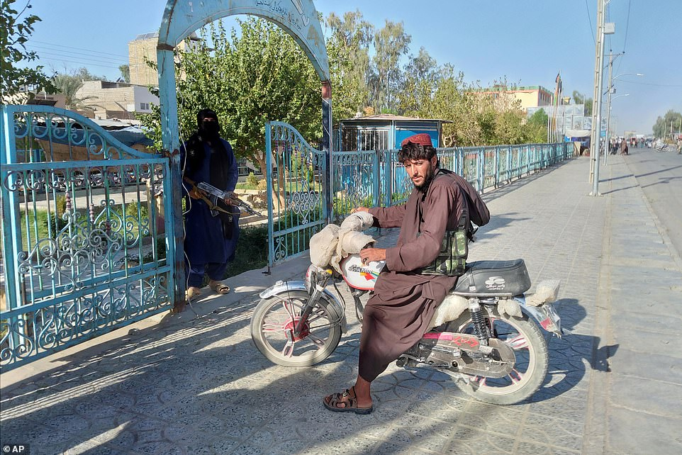 Two Taliban fighters stand guard in the city of Farah, the capital of Farah province, after seizing it two days ago