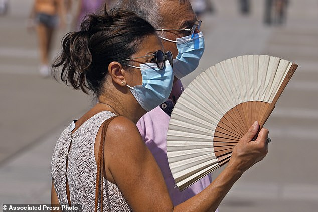 A woman fans herself in Madrid, Spain, Tuesday, as temperatures begin to rise at the start of the heatwave