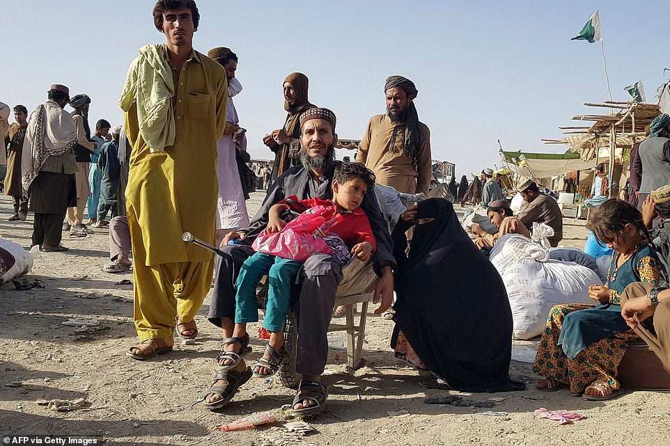An Afghan family at the border crossing with Pakistan in Spin Boldack waits to cross after the border was shut when the Taliban took control of it a week ago