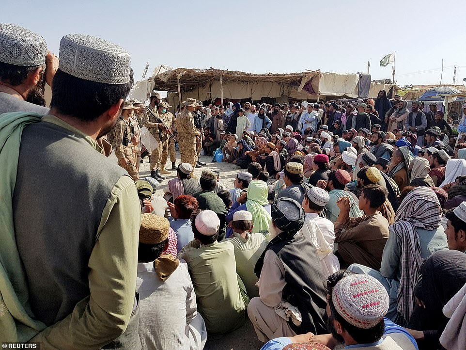 Pakistan's Army soldiers talk with people who gather to cross at the Friendship Gate crossing point in the Pakistan-Afghanistan border town of Chaman