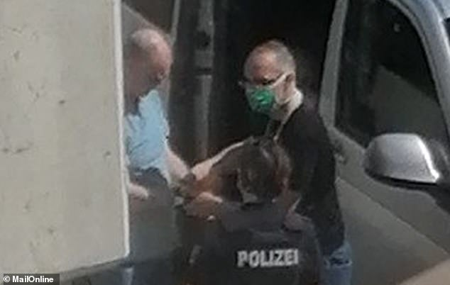 David Smith, 57, (left in the blue t-shirt) worked as a guard at the British embassy in Berlin and was arrested at his flat in Potsdam on Tuesday after a long running investigation by security services in Germany and the UK