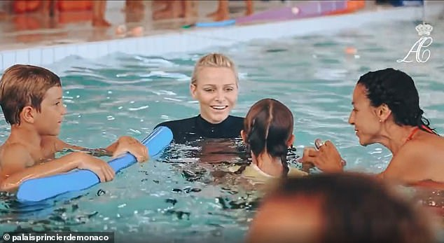 In her element: The former Olympic swimmer flashes a smile as she takes part in a swimming lesson with children on a royal visit