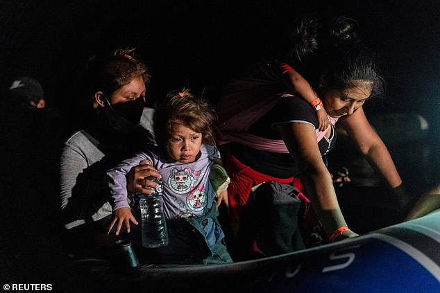 He privately disclosed that the US 'system isn't built' to handle the number of people coming to the border (pictured:Asylum-seeking migrant families disembark from an inflatable raft after crossing the Rio Grande river into the United States from Mexico on August 12th)