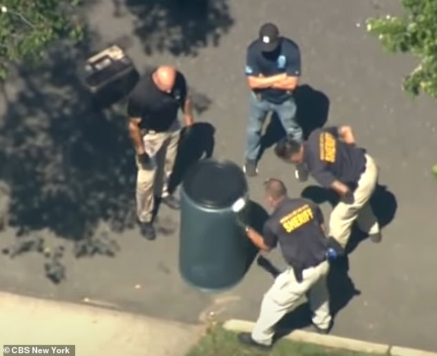 Officers are seen inspecting the green barrel, in footage obtained by CBS News