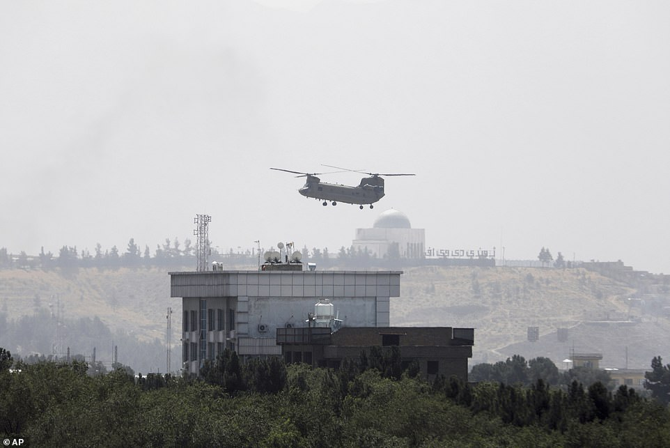 AUS Chinook helicopter flies over the city of Kabul as diplomatic vehicles leave the compound after the Taliban advanced on the Afghan capital, August 15